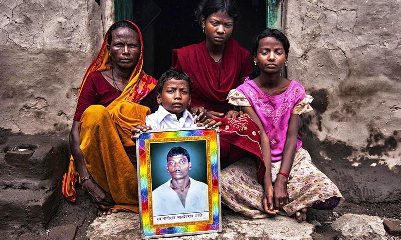 خودکشی کرنے والے ایک کسان کا خاندان اپنے سربراہ کی تصویر کے ساتھ غمزدہ بیٹھا ہے۔ —. فائل فوٹو اوپن سورس میڈیا