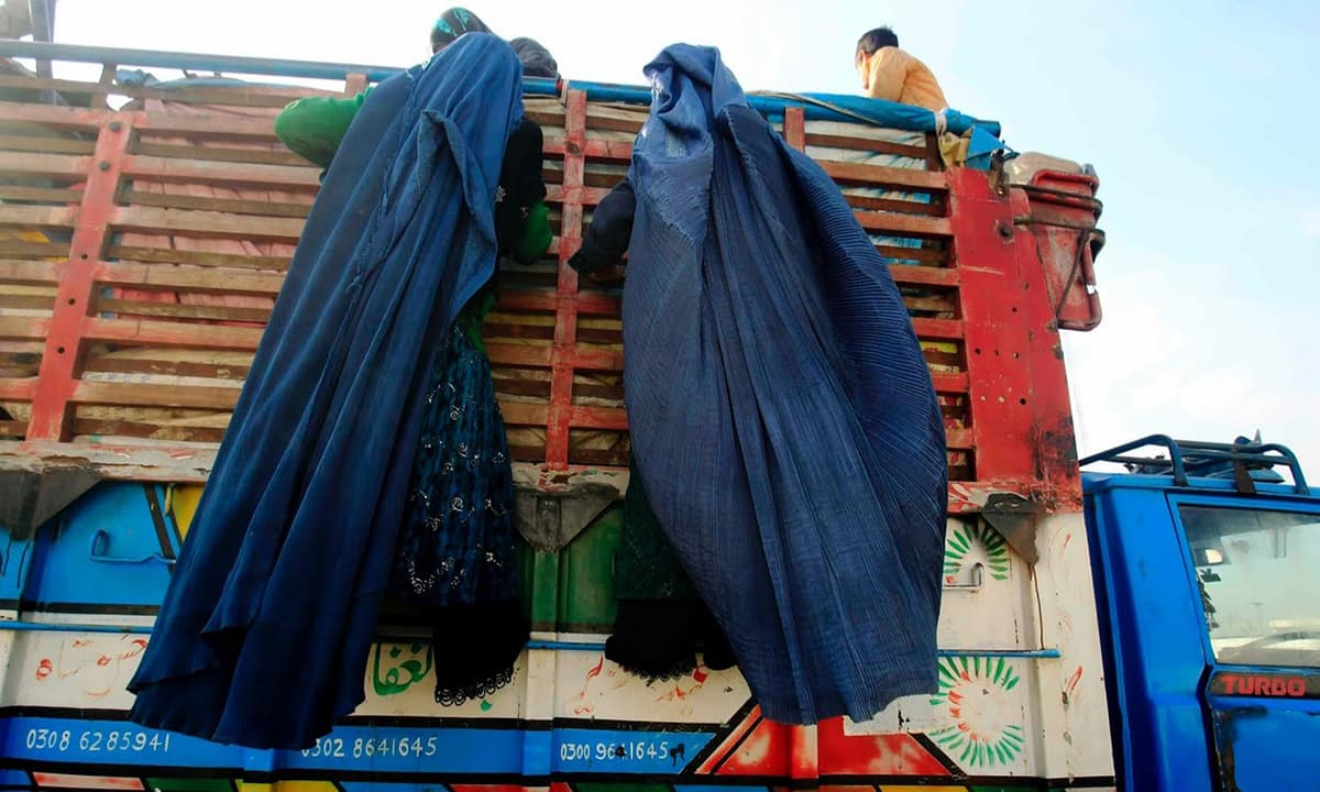 Afghan refugee women climb on a truck to be repatriated to Afghanistan at the United Nations High Commissioner for Refugees (UNHCR) office.