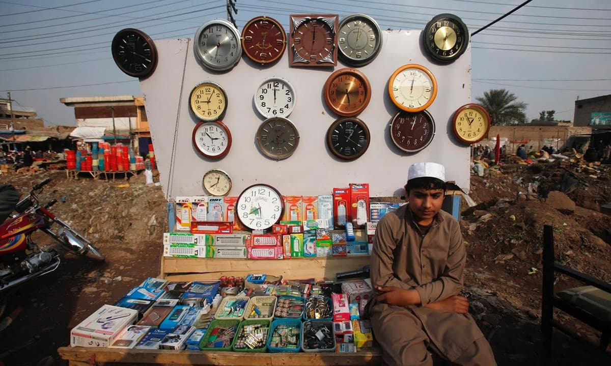 Muhammad Ahmad waits for costumers at his stall. He is an Afghan refugee whose family have a temporary residency card.