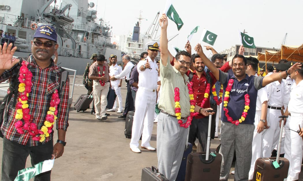 Indian nationals wave Pakistani flags as PNS Aslat arrives at Karachi Port after successful evacuation of stranded Pakistanis and foreign nationals from Yemen. -PN Photo