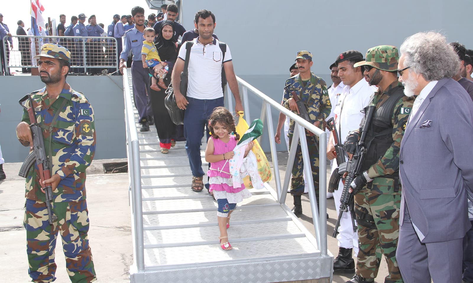 A Pakistani family disembarks as PNS Aslat arrives Karachi Port after successful evacuation of stranded Pakistanis and foreign nationals from Yemen. -PN Photo