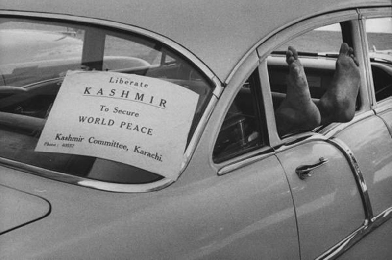 Wake me up when Kashmir's free: A man takes a nap in the backseat of a car with a poster demanding the liberation of Kashmir (from India) in Karachi (1956).