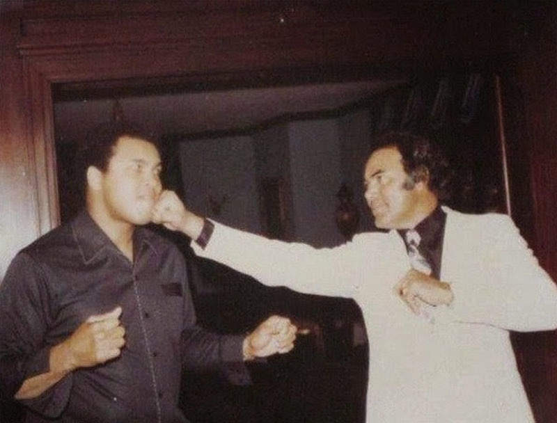 Dhishoom! Pakistani action film hero, Sultan Rahi, jokes with former heavyweight boxing champion, Mohammad Ali in Lahore. Ali was visiting Pakistan in 1988.