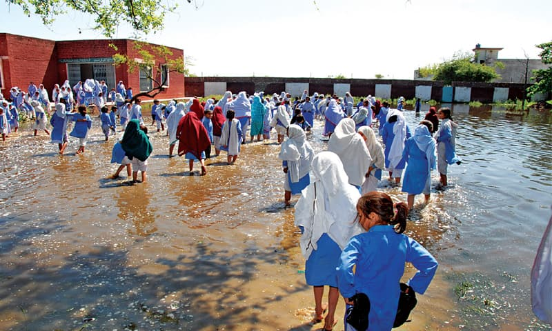 SIALKOT: Students wade through sewage accumulated in the ground of their school at Seehowal, Pasrur. — Dawn