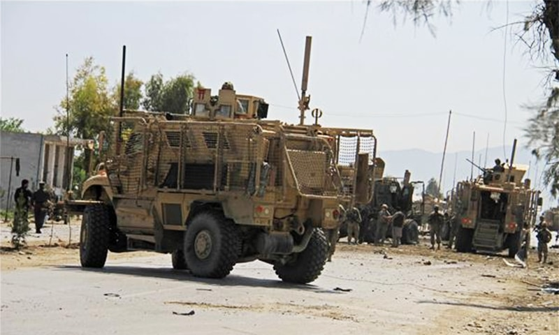 Afghan andUS soldiers gather at the site of a suicide attack that targeted a convoy in Jalalabad ─ AP