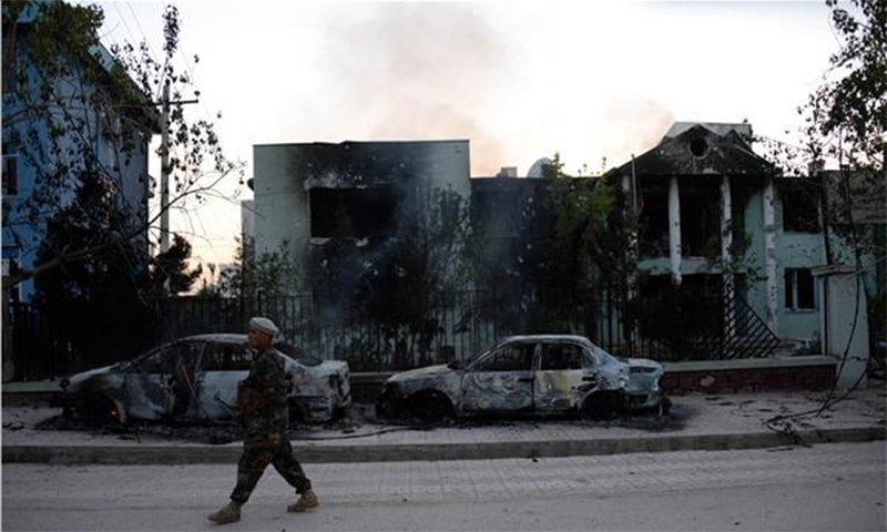 An Afghan security personnel walks past damaged cars in front of a court complex following a suicide attack in Mazar-i-sharif ─ AFP