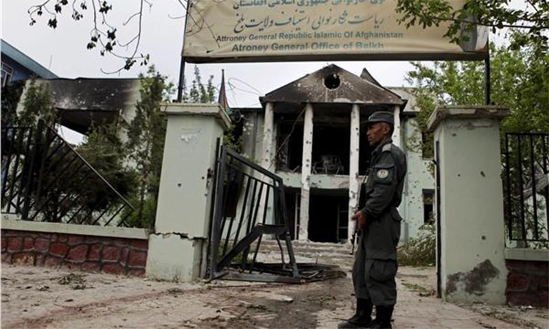 An Afghan policeman stands guard outside of court a day after a Taliban attack, in Mazar-i-Sharif ─ Reuters