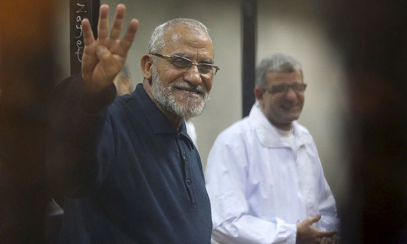 Muslim Brotherhood's Supreme Guide Mohamed Badie (L) flashes the Rabaa sign as he stands behind bars during his trial with ousted Egyptian President Mohamed Morsi and other leaders of the brotherhood at a court in the police academy on the outskirts of Cairo in this December 14, 2014 file photo. - Reuters