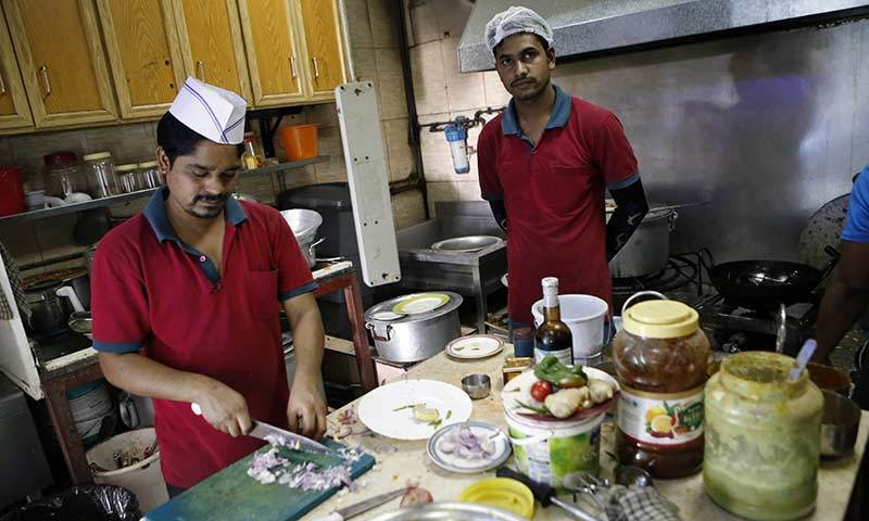 Workers cook food in 'Zaiqa'.— AFP