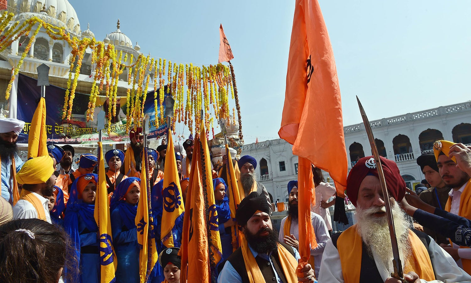 Priests march at the Gurdwara Panja Sahib, one of Sikhism's most holy places.— AFP