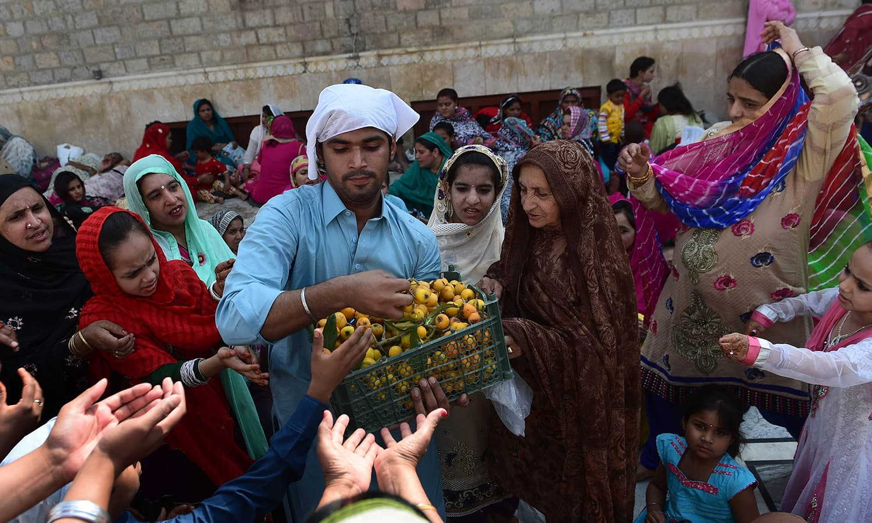A man distributes loquat fruit to pilgrims.— AFP