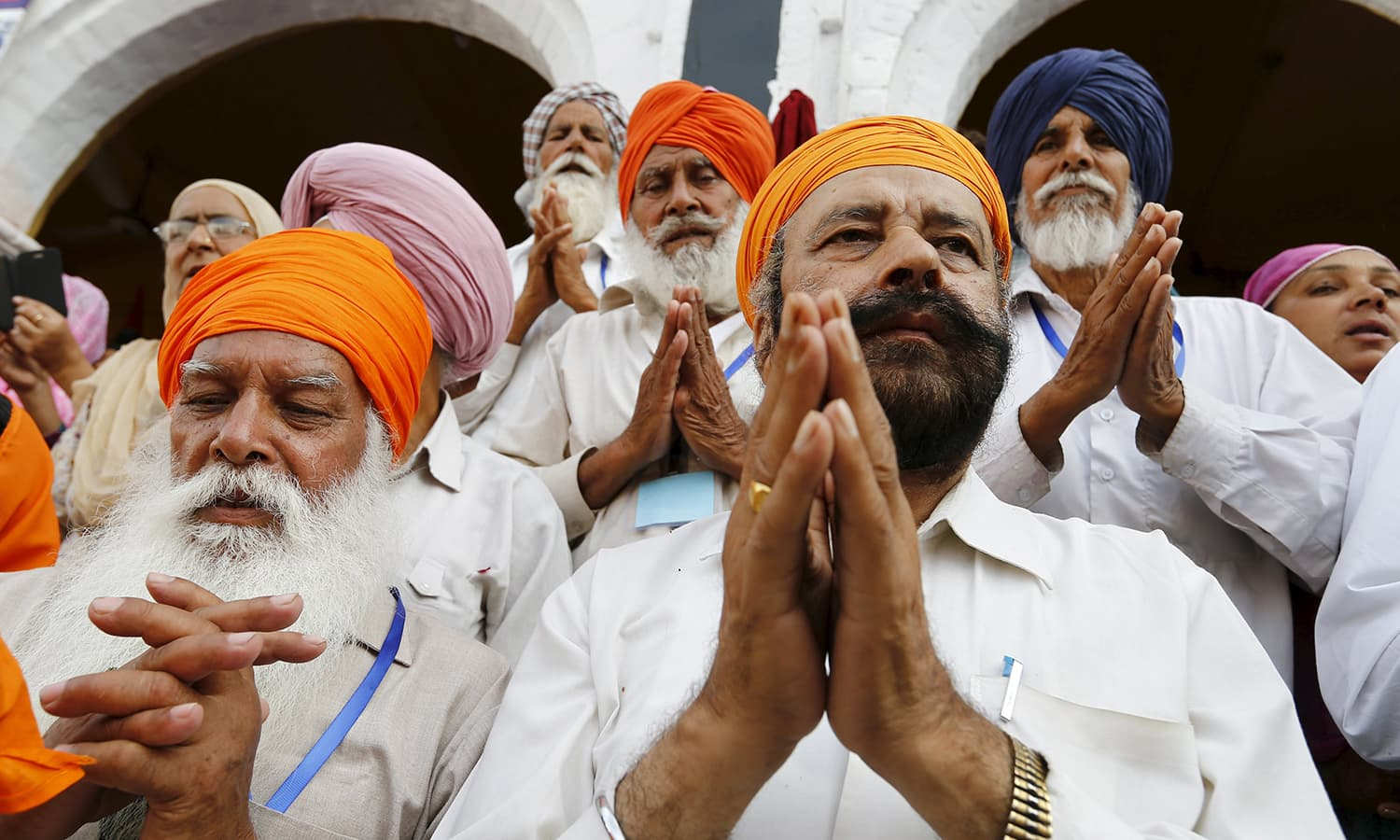Devotees gesture in prayer as the procession passes by during the Baisakhi festival at Panja Sahib shrine in Hassan Abdal. — Reuters