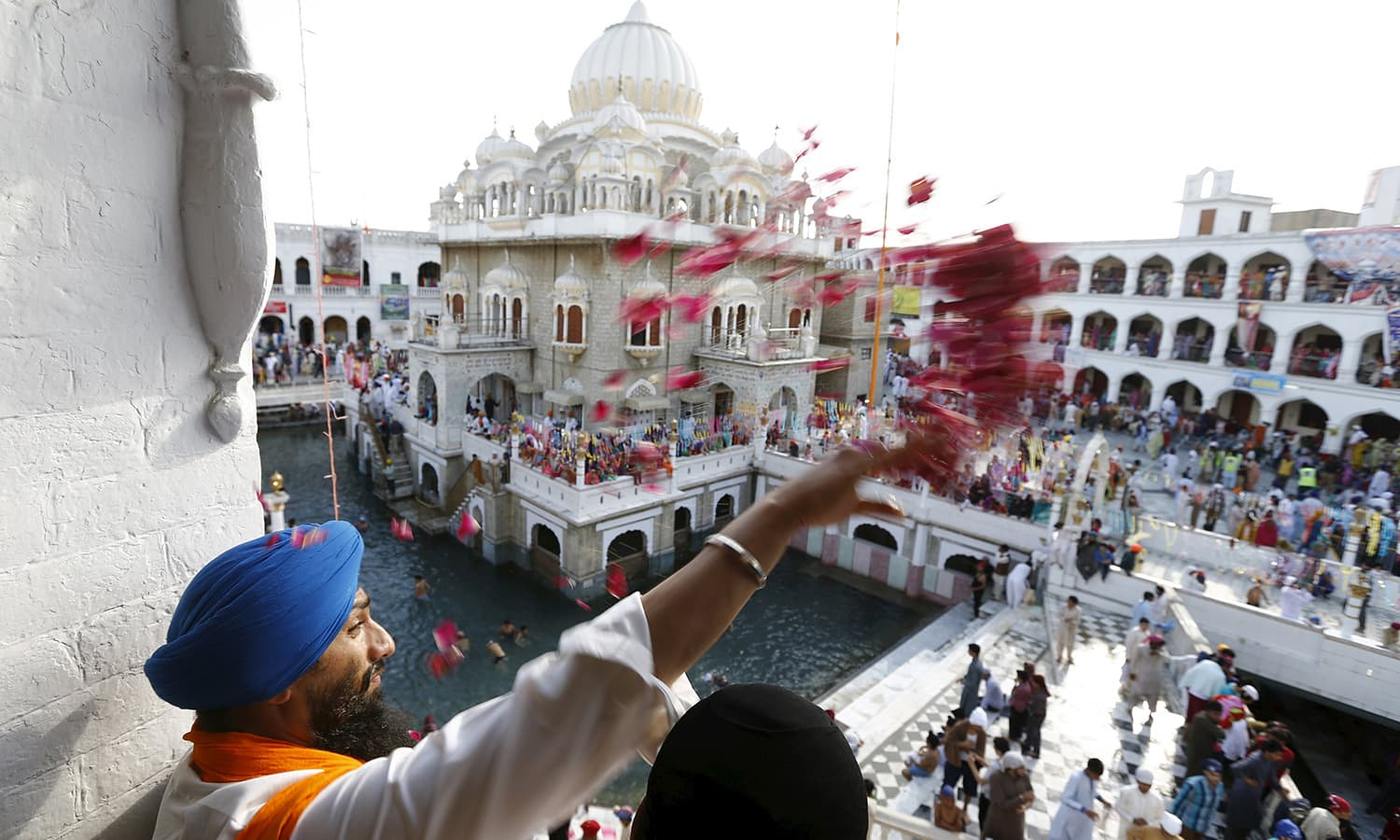 A Sikh devotee throws flower petals as the procession passes by during the Baisakhi festival at Panja Sahib shrine in Hassan Abdal.— Reuters