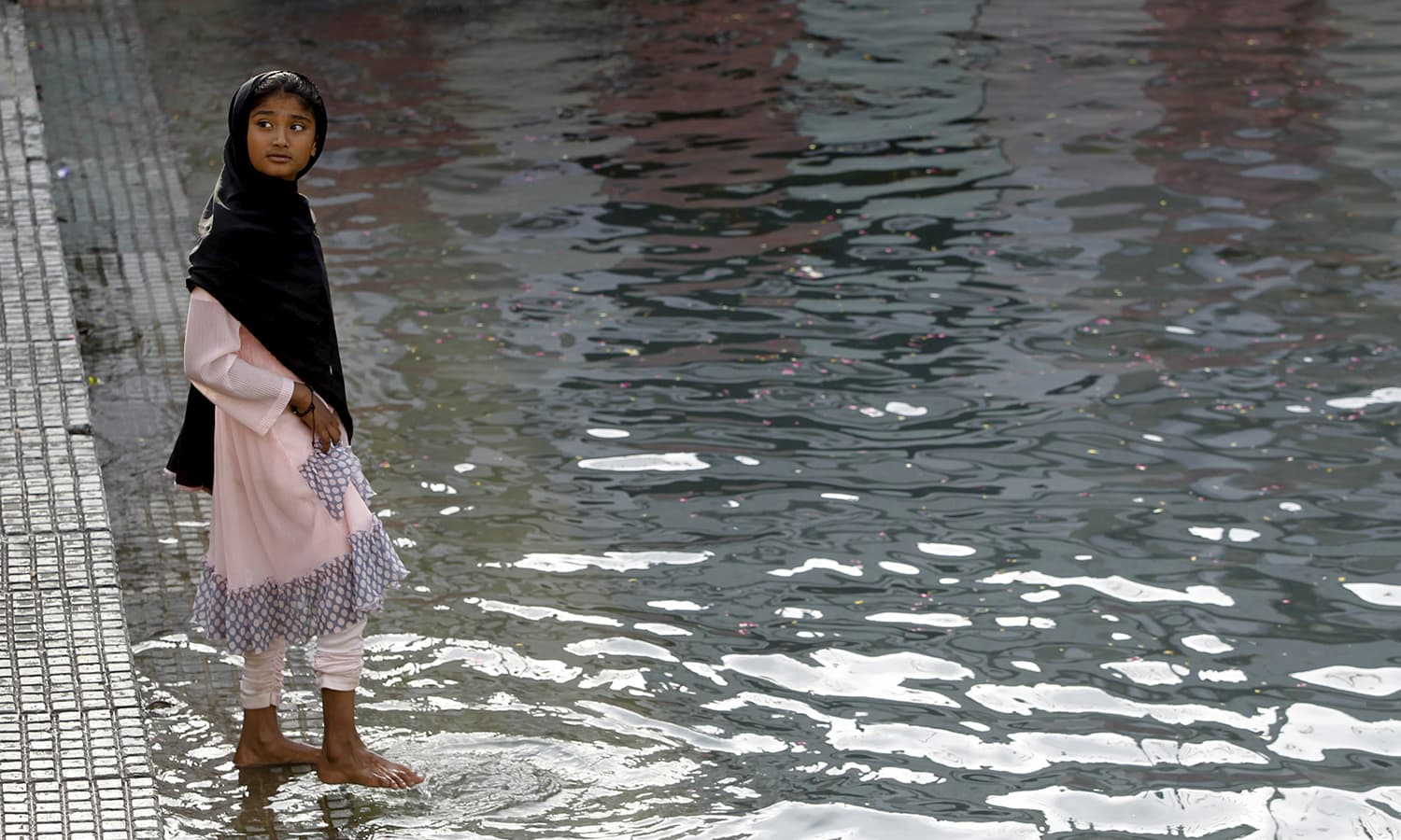 A devotee wets her feet in the holy water.— Reuters