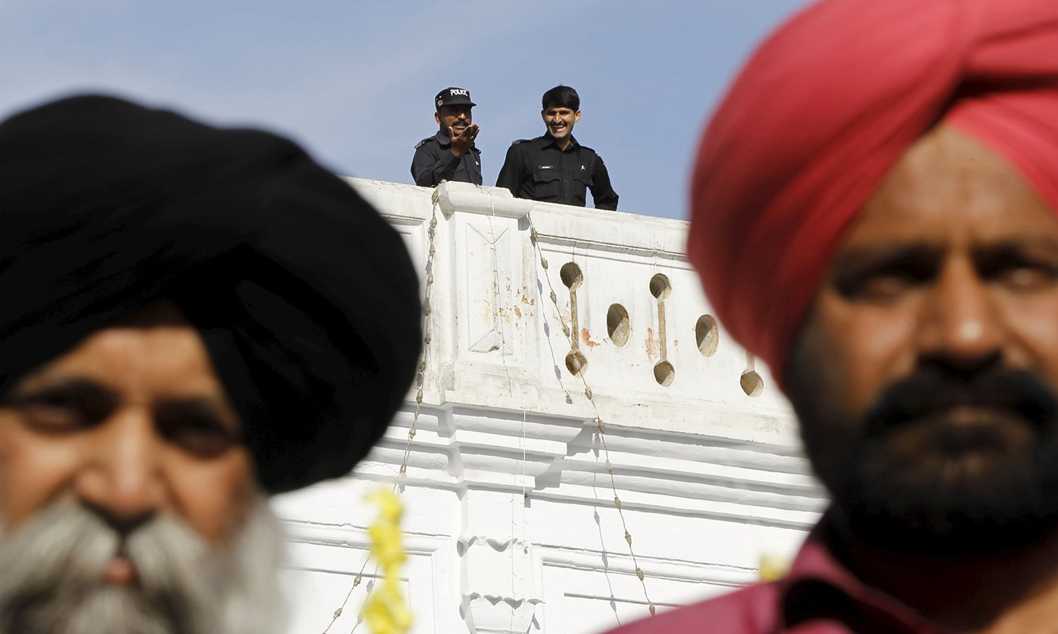 Pakistani police stand guard as Sikh devotees participate in the Baisakhi festival at Panja Sahib shrine in Hassan Abdal.— Reuters