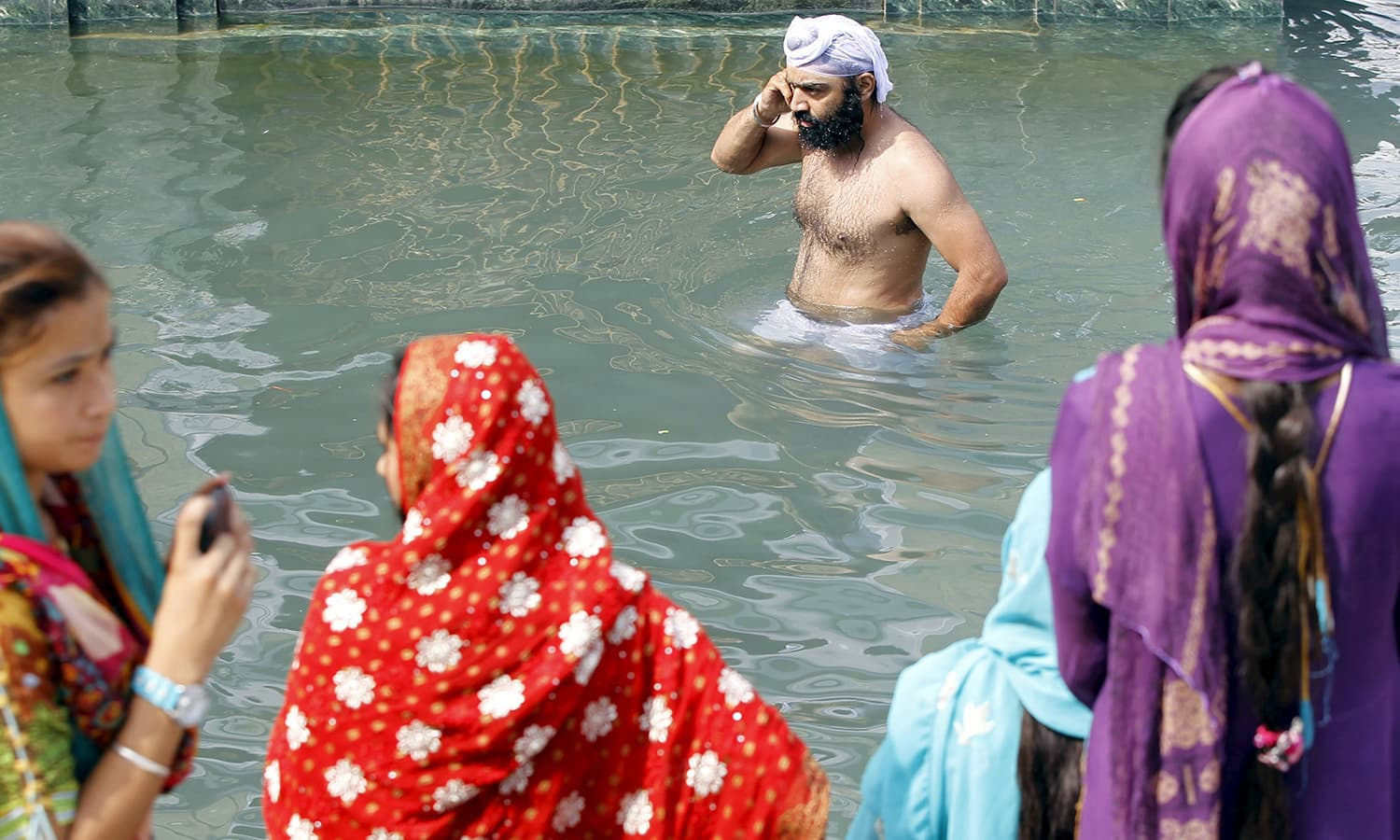 A Sikh devotee washes himself in the holy water.— Reuters