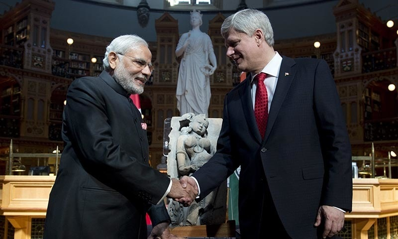 """Canadian Prime Minister Stephen Harper, right shakes hands with Indian Prime Minister Narendra Modi as Harper returns a sculpture of a woman known as """"parrot lady"""" at the Parliamentary Library on Parliament Hill in Ottawa, Wednesday April 15, 2015. — AP"""