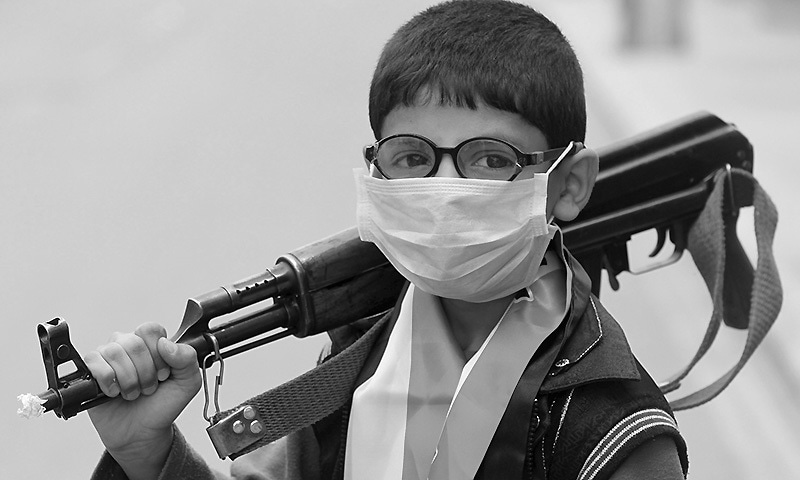 A boy wearing a surgical mask holds a weapon.— Reuters