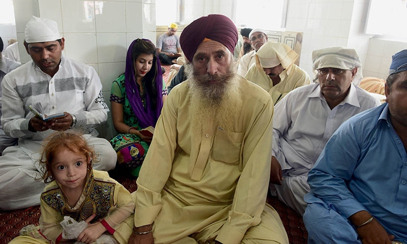 In this photograph taken on April 14, 2015, Harbhan Singh (C), who migrated from restive Tirah Valley in Khyber tribal agency go to flee a military operation, sits at the Gurdwara Panja Sahib in Hasanabdal, during the annual Baisakhi festival. — AFP