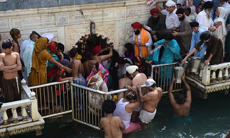 In this photograph taken on April 14, 2015, Sikh pilgrims gather around the imprinted Guru Nanak hand at the Gurdwara Panja Sahib in Hasanabdal, during the annual Baisakhi festival. — AFP