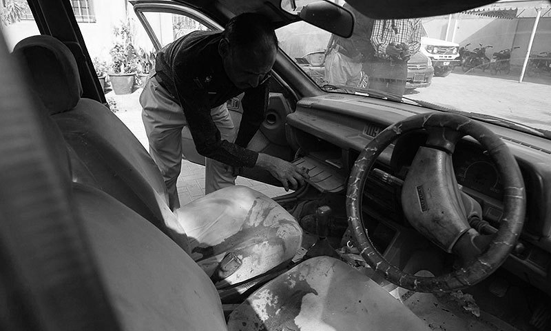 A police officer examines US citizen Debra Lobo's car, targeted by gunmen in Karachi on Thursday. —AP