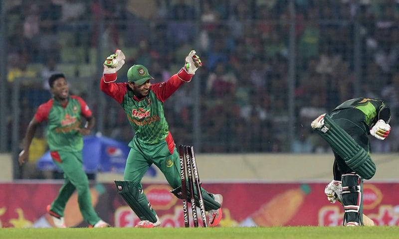Bangladesh cricketer Mushfiqur Rahim (C) reacts after the dismissal of Pakistan cricketer Mohammad Hafeez (R).—AFP