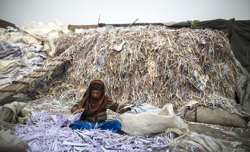 An Afghan girl sorts papers before they are taken to a recycling factory in Lahore | Reuters