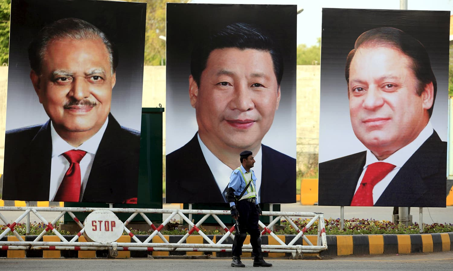 A policeman stands guard next to giant portraits of (L-R) Pakistan's President Mamnoon Hussain, China's President Xi Jinping, and Pakistan's Prime Minister Nawaz Sharif, displayed along a road ahead of Xi's visit to Islamabad April 19, 2015.— Reuters