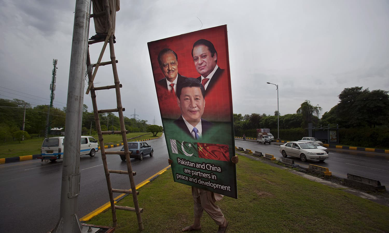 A Pakistani worker hangs a billboard showing pictures of Chinese President Xi Jinping, center, with Pakistan's President Mamnoon Hussain, right, and Prime Minister Nawaz Sharif welcoming Xi Jingping's to Islamabad. — AP