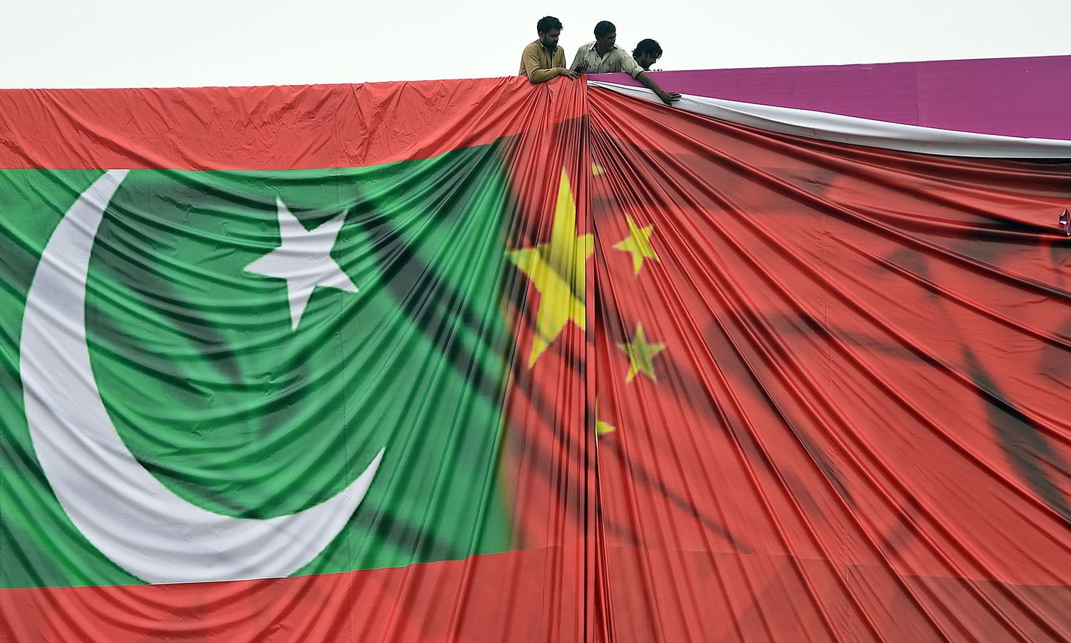 Labourers arrange a welcome billboard featuring the Chinese and Pakistani national flags ahead of the forthcoming visit by Chinese President Xi Jinping.— AFP