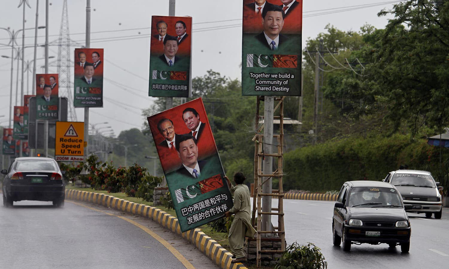 A worker hangs a billboard showing pictures of Chinese President Xi Jinping, center, with Pakistan's President Mamnoon Hussain, left, and Prime Minister Nawaz Sharif welcoming Xi Jingping to Islamabad, Pakistan, Sunday, April 19, 2015.— AP
