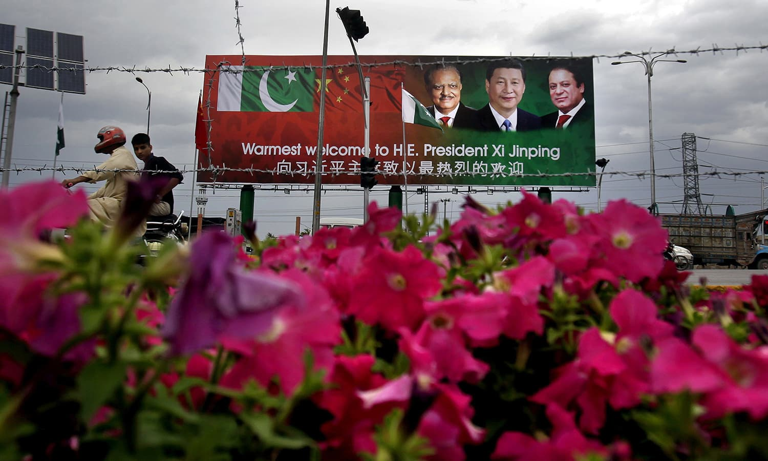 A motorcyclist rides past a billboard showing pictures of Chinese President Xi Jinping, center, with Pakistan's President Mamnoon Hussain, left, and Prime Minister Nawaz Sharif welcoming Xi Jingpin to Islamabad.— AP