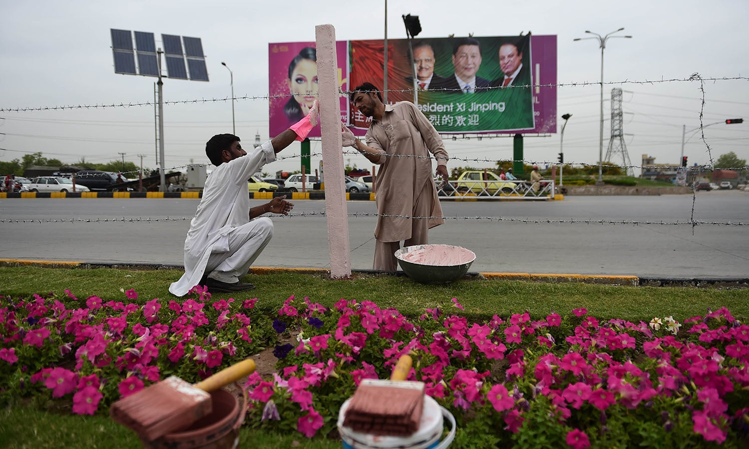 Labourers decorate the roadside in front of a welcoming billboard.— AFP