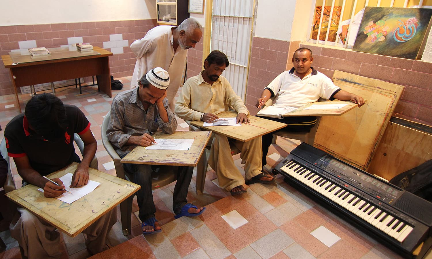 The interior of the school is like an exquisite art gallery where paintings hang on the walls and air conditioners run all the time. Kazim, who has been studying at the school for the past eight years, is seen guiding a student about his sketch work.