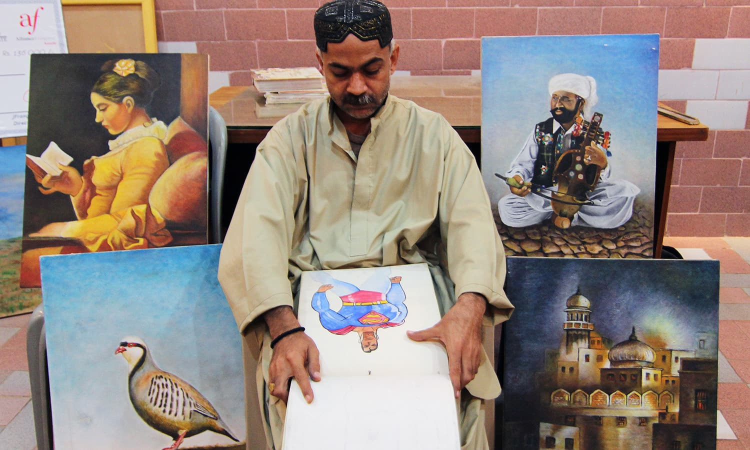 Learning art was a first-time experience for Abdul Aziz Bugti, whose village Dera Bugti, had no proper schools, let alone art schools. In this photograph he sits surrounded by paintings he has made in the past year.