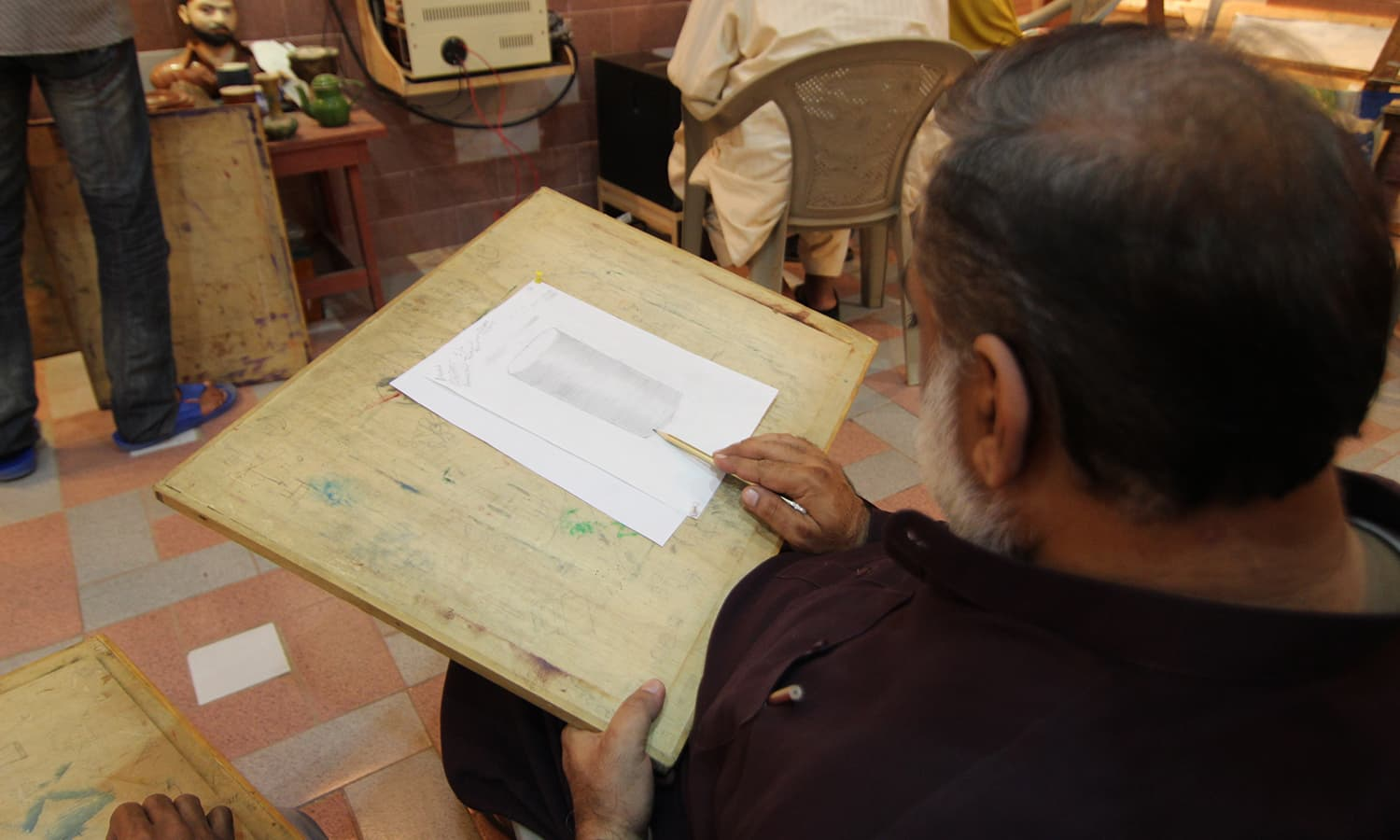 A student sketches on his canvas.