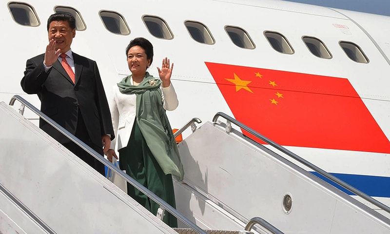 Chinese President Mr Xi Jinping and the First Lady Peng Liyuan wave upon their arrival in the capital amid a grand welcome. —AFP