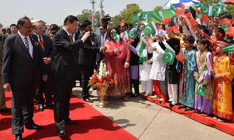 President Xi Jinping waves at children greeting him upon arrival at Nur Khan air base. —AFP