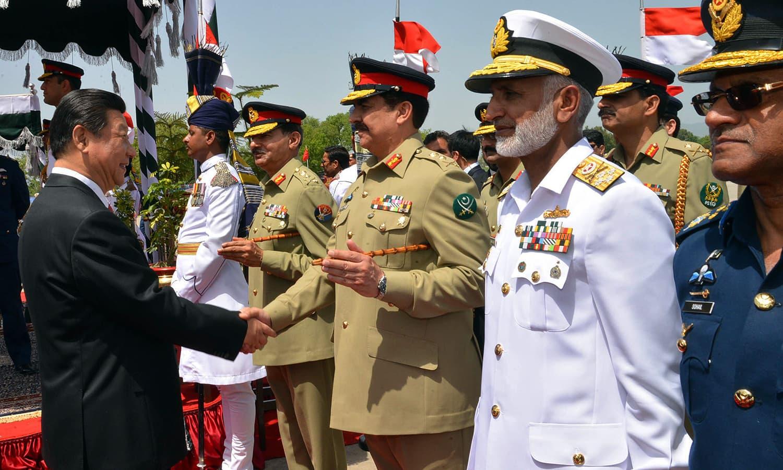 Xi Jinping shakes hands with Army Chief Raheel Sharif after arriving at Nur Khan air base in Rawalpindi. — AFP