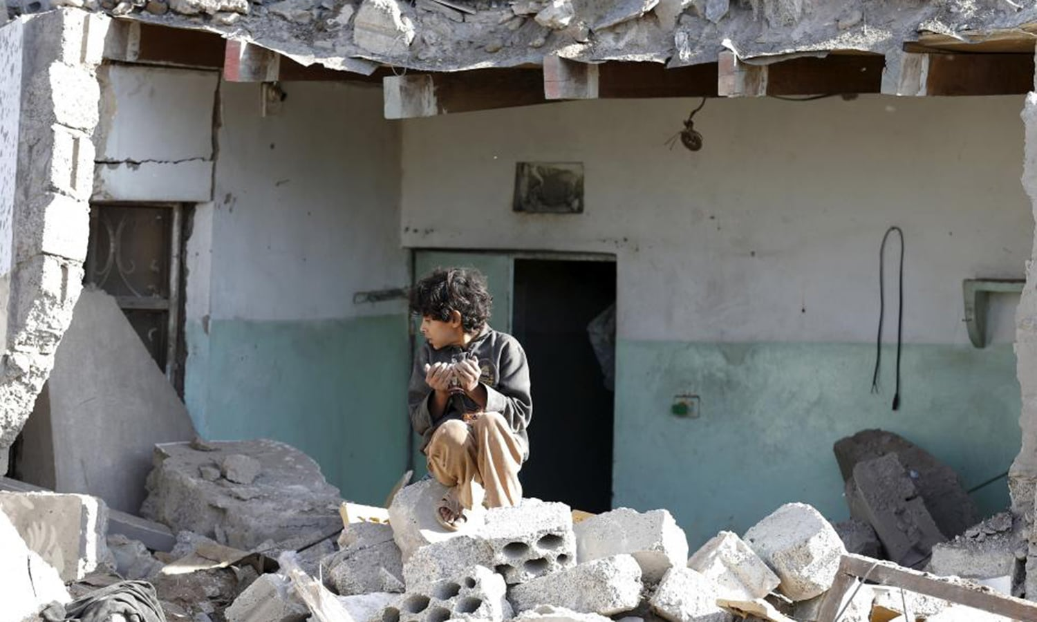 A boy sits at the site of an air strike at a residential area near Sanaa Airport. — Reuters/File