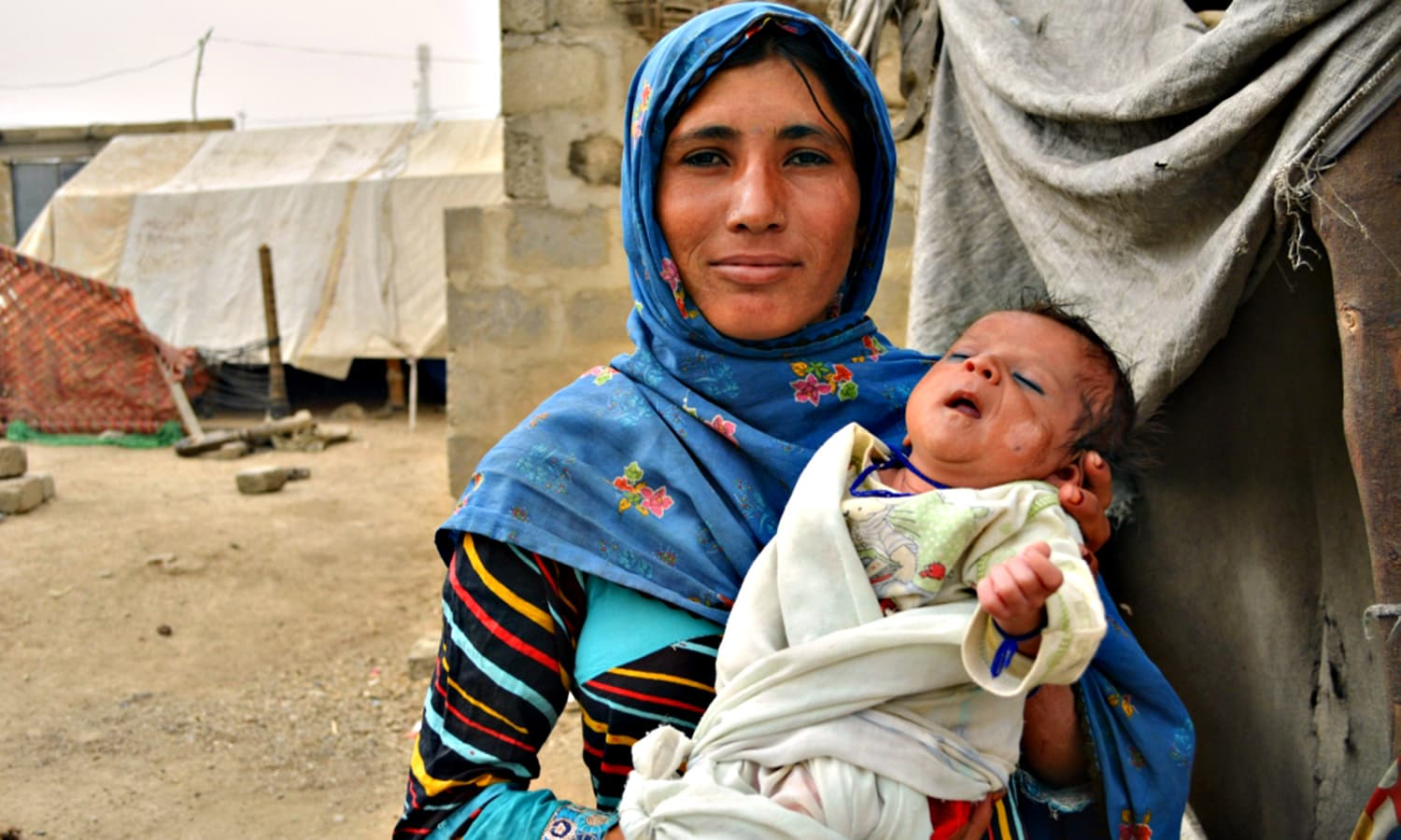 Rubina Hisbani with her two month old son Hakim Ali, outside her makeshift hut in the Sindhabad slum.