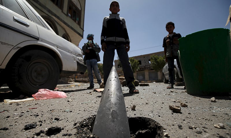 Boys stand in front of an artillery shell partially buried in the ground along a street damaged by an air strike on Monday that hit a nearby army weapons depot, in Sanaa on April 21, 2015 ─ Reuters