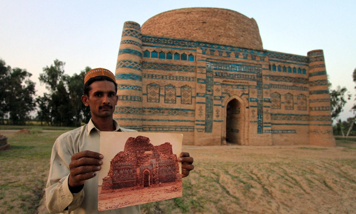 Inayatullah shows a photo of the tomb before restoration