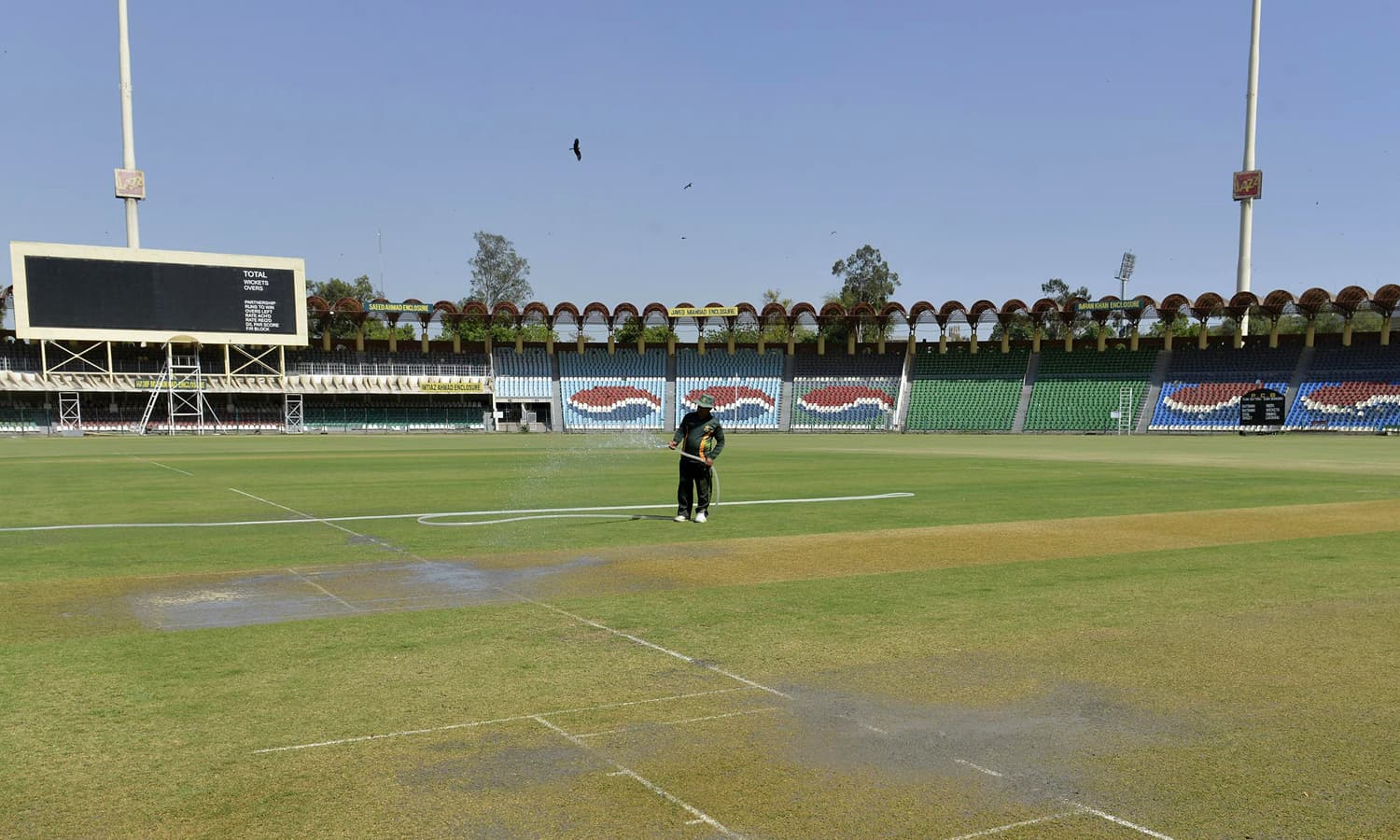 A groundskeeper waters the pitch at the Gaddafi Cricket Stadium in Lahore. — AFP
