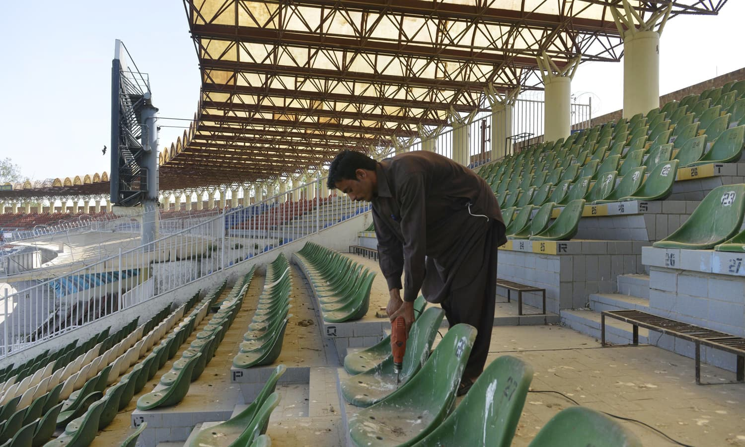 Maintenance staff repair seats at the Gaddafi Stadium. — AFP