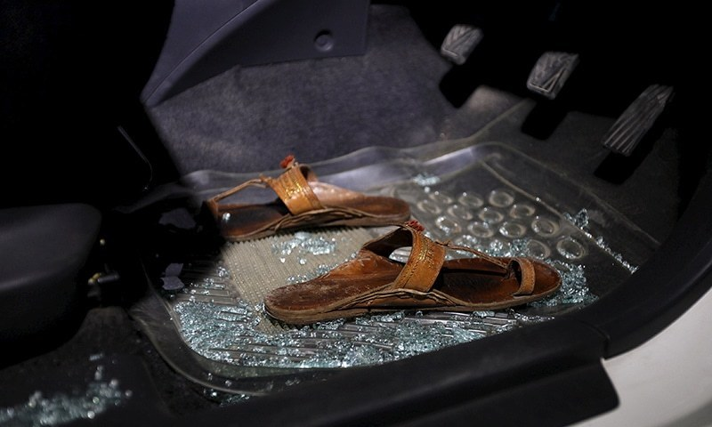 A pair of sandals lies amid broken glass in a car after the murder of Sabeen Mahmud in Karachi, Pakistan, April 25, 2015. — Reuters