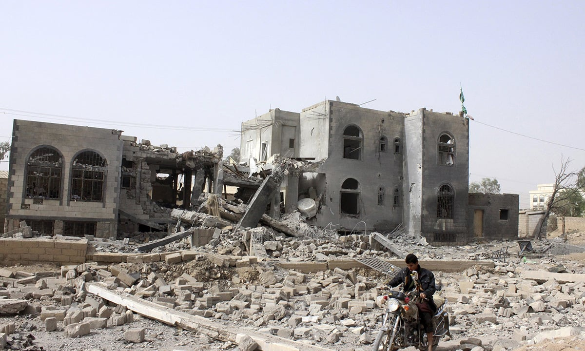 A man rides a motorcycle past a headquarters of the Houthi group, which was destroyed after an air strike by a Saudi-led coalition, in Yemen's northwestern city of Saada April 26, 2015. — Reuters/file