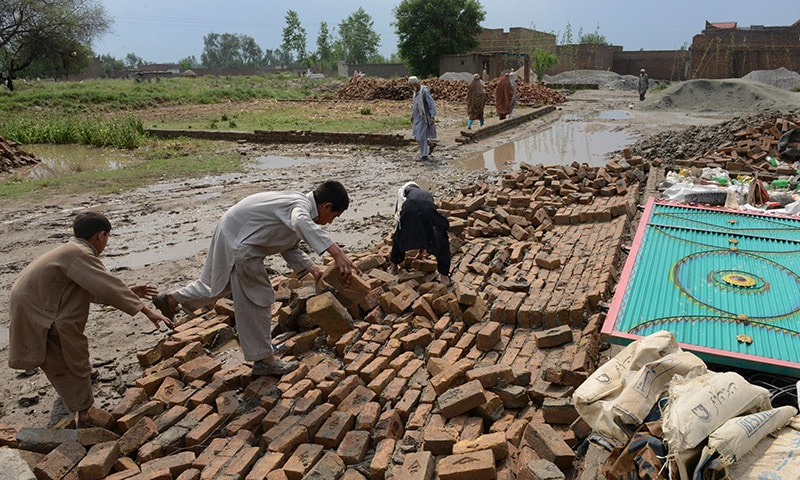 Pakistani residents collect bricks after their house collapsed following heavy rain and winds in Peshawar on April 27, 2015. —AFP