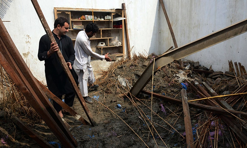 Pakistani residents collect belongings at their home after it was damaged in heavy rain and winds in Peshawar on April 27, 2015. —AFP