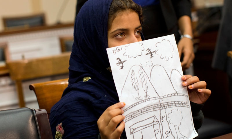 Oct 29, 2013: At a news conference on Capitol Hill in Washington, nine-year-old Nabila Rehman holds a photo with a drawing she made depicting a drone strike that killed her grandmother. — AP